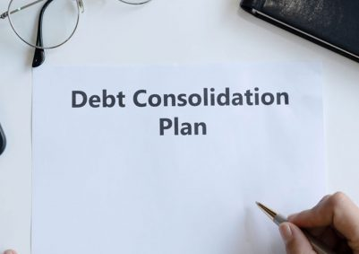 Man about to write on a sheet with 'Debt Consolidation Plan' printed on it