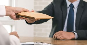 Man in grey suit hands a folded brown envelope to man in white business shirt