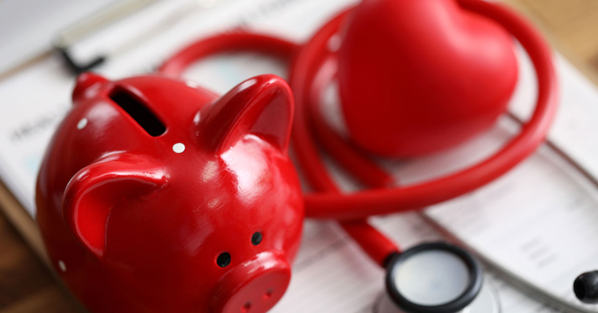 Red piggybank on a desk beside a red stethoscope