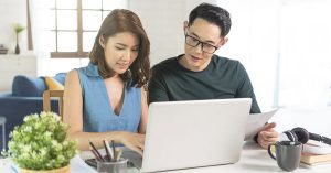 Young couple working together on laptop in their home
