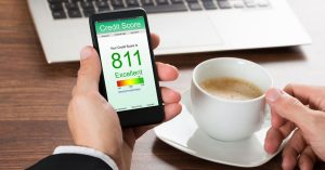 Man holding smartphone showing Excellent credit score beside a cup of tea