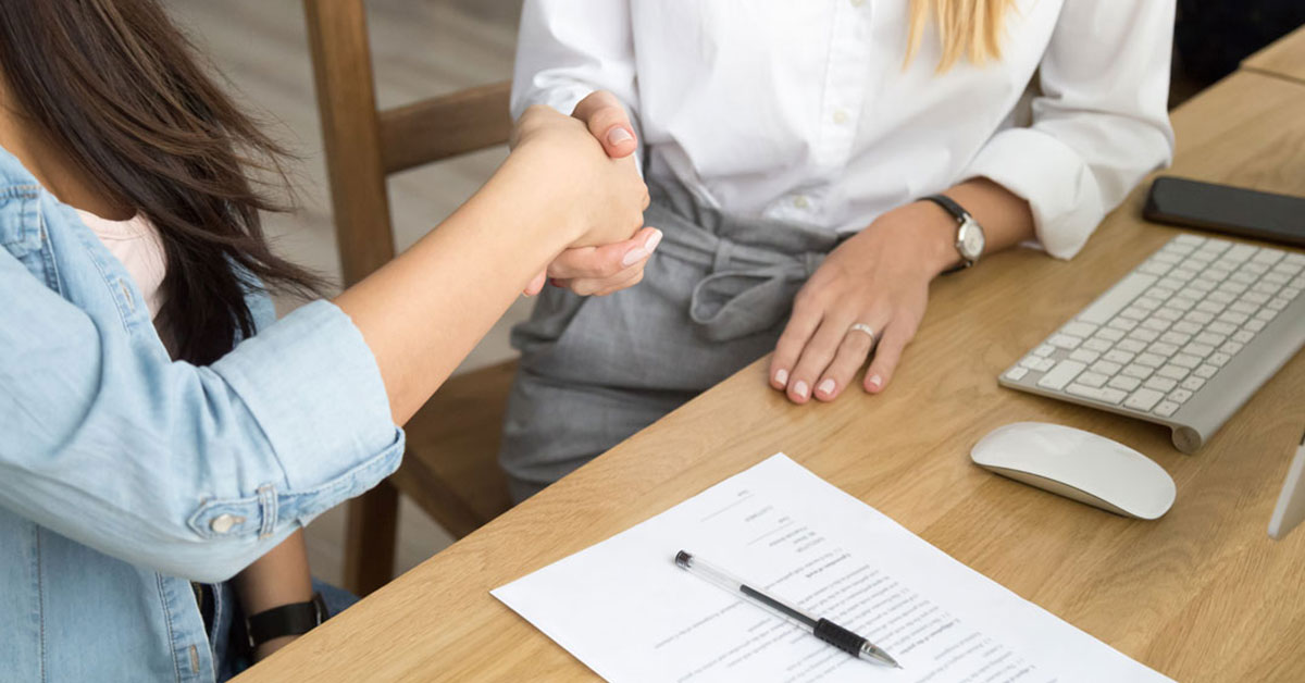 Close-up of handshake between two women at a desk with a contract document on it