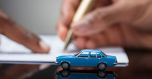 Blue model car on a desk as a man shows another man where to sign on a contract