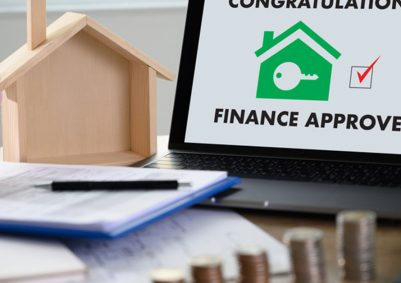 Laptop screen reads 'Finance Approved' with a tick and graphic of a home