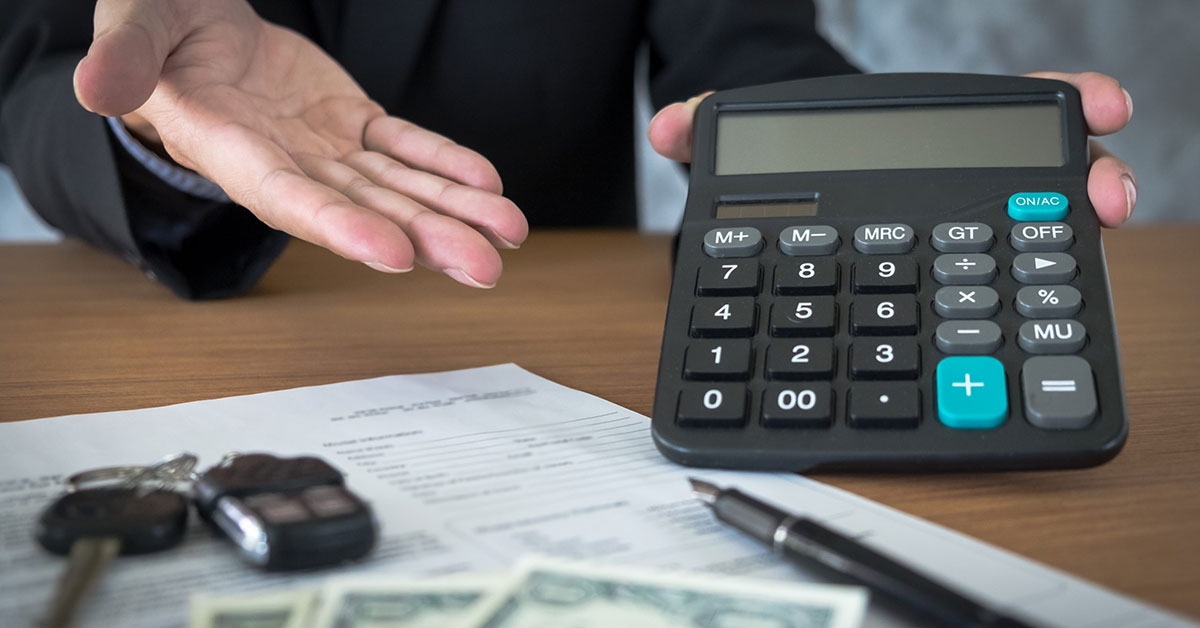 Executive in black suit shows a calculator above a contract, pen, and car keys
