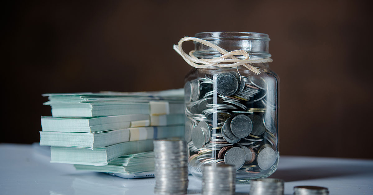 Glass jar full of silver coins beside stacks of coins and wads of cash