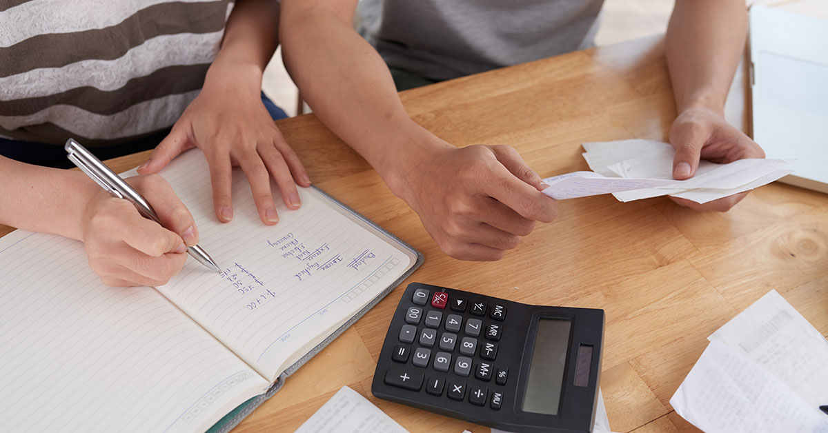 Close-up top view of man's hands holding bills as a woman makes notes