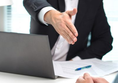 Man in black suit extends his hands for a handshake above a laptop and documents on a desk
